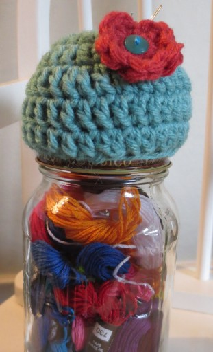 A pin cushion on the lid of a mason jar. If you`re bored, you can stare REALLY hard and try to see the needle in the cushion.