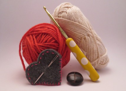 Still life entitled Wool, Size 5mm hook, Button and Darning Needle. Also, coincidentally, all the supplies you`ll need for this project.